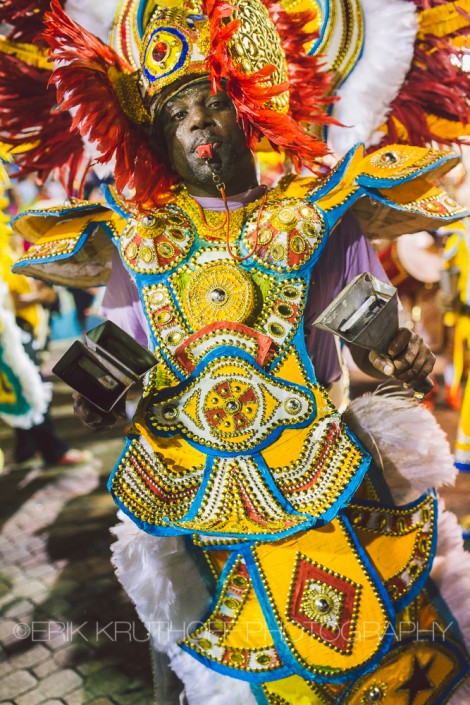 a costumed man plays the cow bells in a junkanoo rush out in nassau