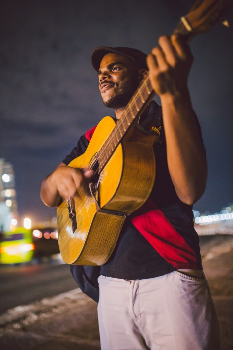 man playing a guitar and singing in Havana