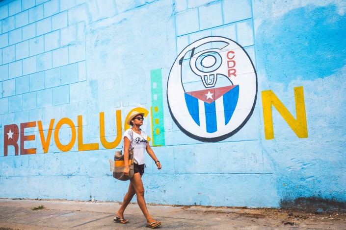 A photograph of a woman walking on the street in front of a Socialist propaganda mural in cienfuegos, cuba