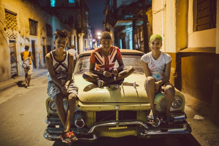 three teenagers sitting on a classic car in Havana, Cuba