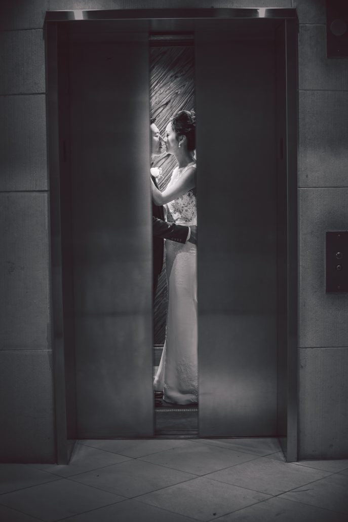 wedding portrait of bride and groom kissing in the elevator at Atlantis paradise island bahamas