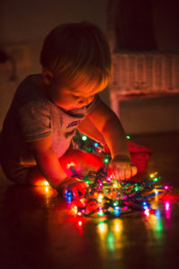 child playing with christmas lights