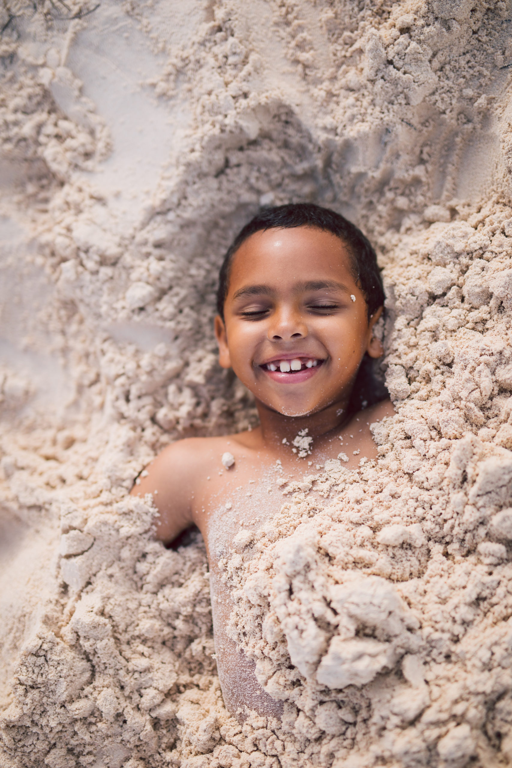 child buried in the sand at the beach