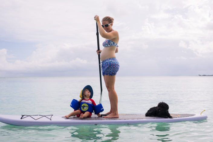Pregnant woman on a stand up paddle board with her child and dog