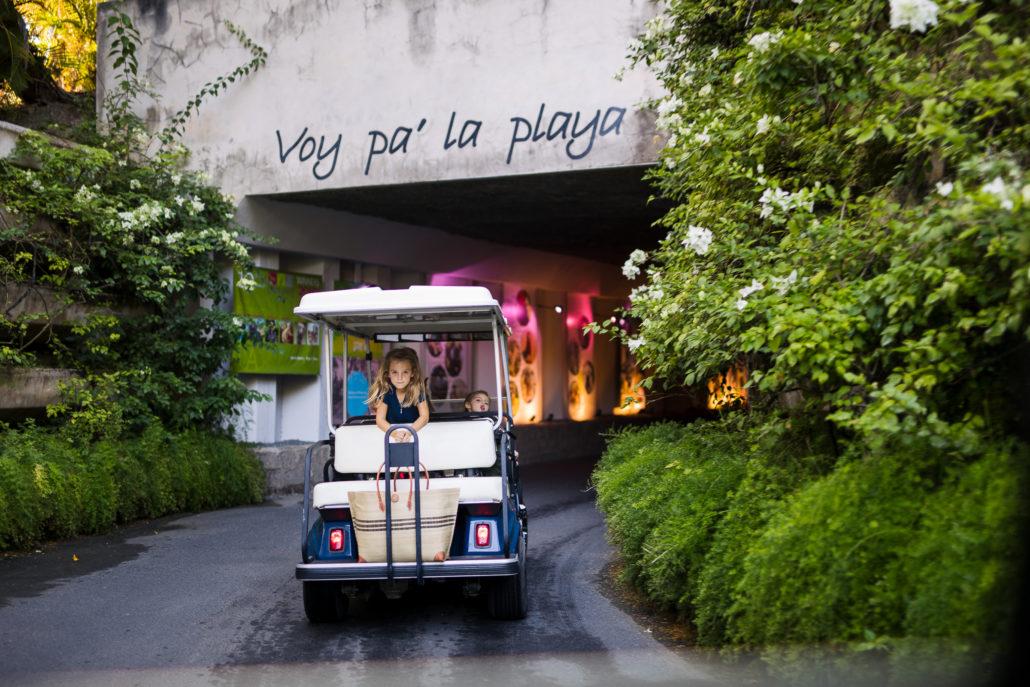 Girl riding in a golf cart on the way to the beach at Ritz-Carlton Dorado Beach