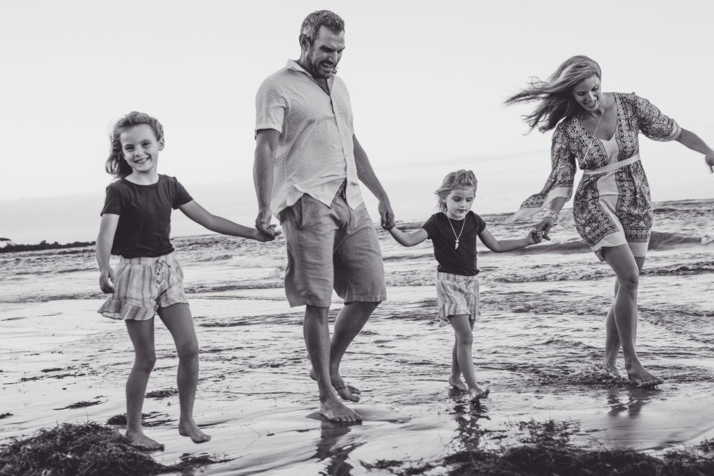 Family portrait of walking on the beach together in Dorado, Puerto Rico