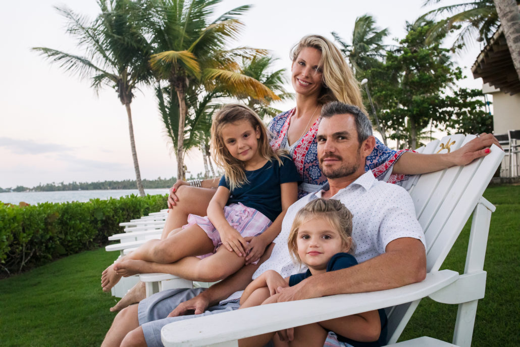 Family portrait by Erik Kruthoff of a family sitting on adirondack chairs at Ritz-Carlton Dorado Beach, Puerto Rico
