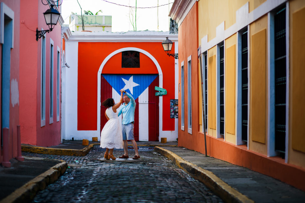 a photograph by Erik Kruthoff of a couple dancing in Old San Juan in front of a Puerto Rico flag