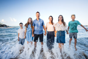 family standing together in the ocean as a wave crashes at their feet