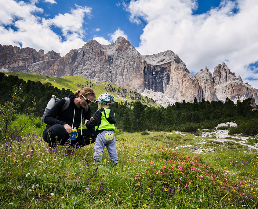 Mother ans Son playing in wildflowers in the mountains of northern Italy
