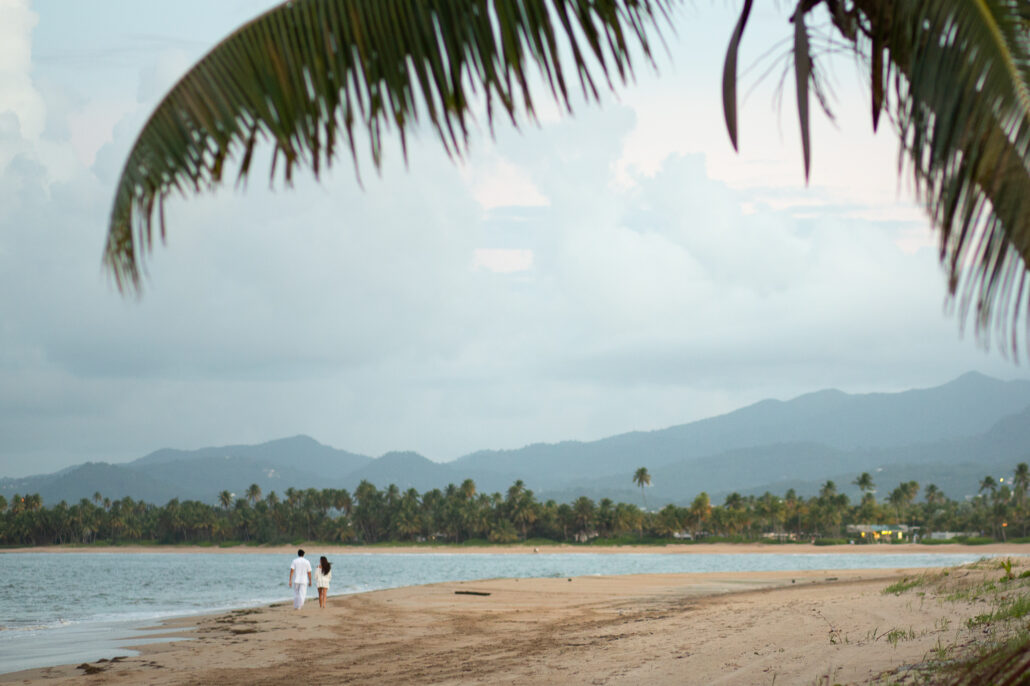 couple walking on the beach at bahia st regis puerto rico